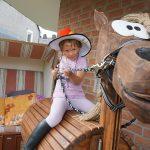 Kind auf Holzpferd